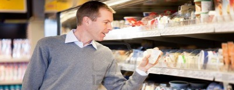 9886982-a-man-buying-cheese-and-comparing-prices-in-a-grocery-store